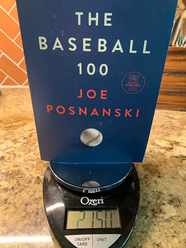An advance copy of Joe Posnanski's upcoming book, The Baseball 100, on a scale showing it weighs 2.15 pounds