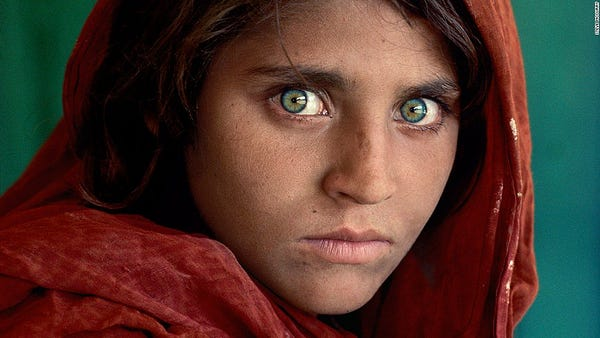 Famous 1985 National Geographic Afghan Girl photo, adolescent girl with piercing green eyes wearing red headscarf