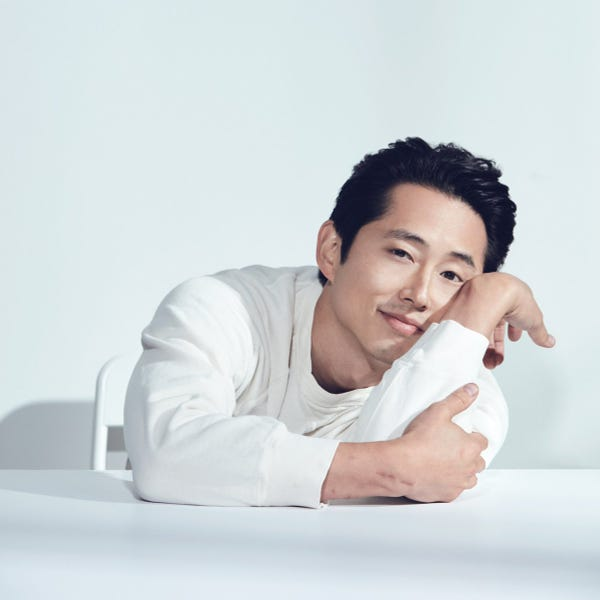 Steven Yeun in all white leaning on a white table. He is sitting in front of a white background.