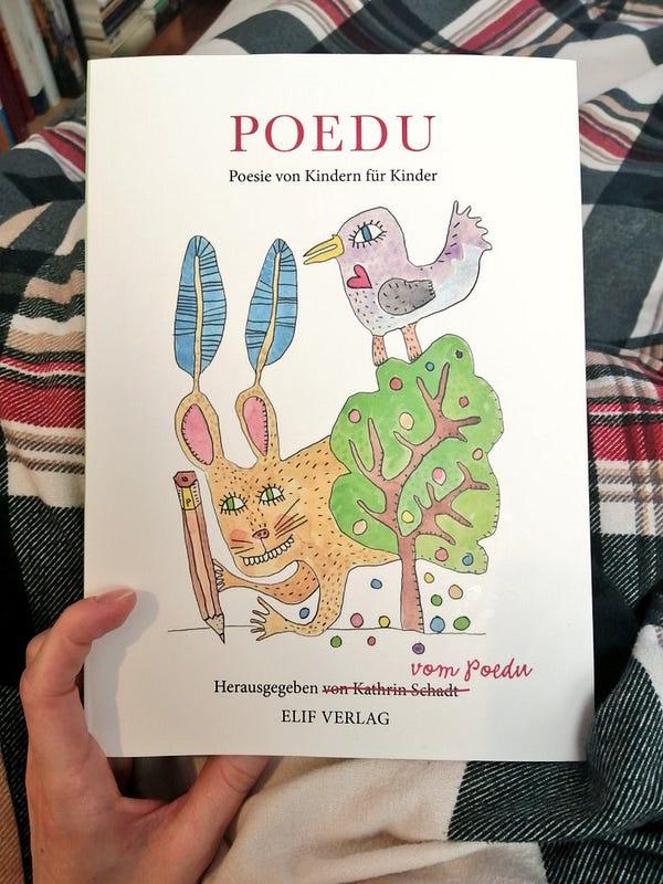 """Meine linke Hand hält das Buch """"POEDU: Poesie von Kindern für Kinder"""" aus dem Elif Verlag"""