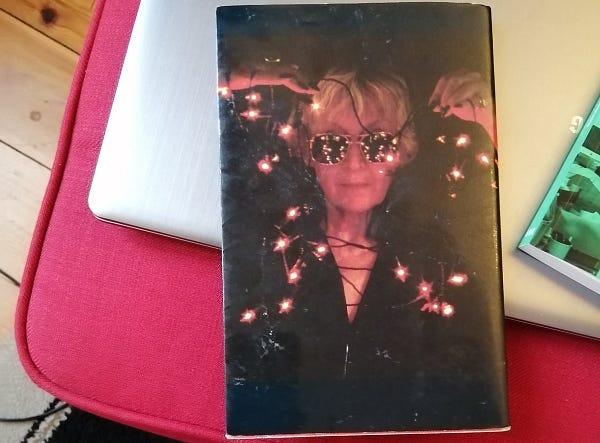 Auf meinem roten Fußschemel liegt mein silberner Laptop, darauf liegt ein Buch mit dem Cover nach unten, der Buchrücken zeigt das Foto einer Frau mittleren Alters mit kurzen blonden Haaren, die eine verspiegelte Sonnebrille trägt und eine verhedderte leuchtende Lichterkette hochhält. Die Lichter spiegeln sich in ihrer Brille.