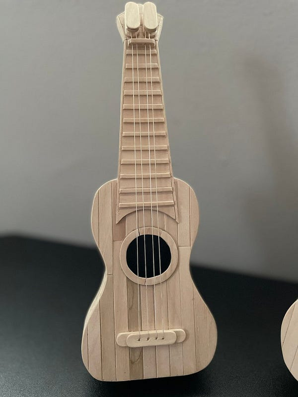 Picture of a ukulele against a black and gray background, made fully out of popsicles.