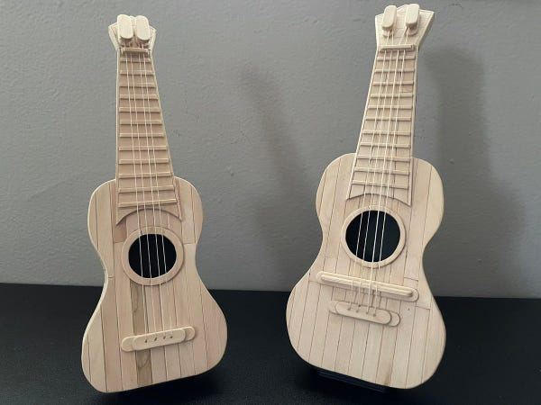 Picture of two wooden ukeleles against a black and gray background. They are made fully out of popsicles.