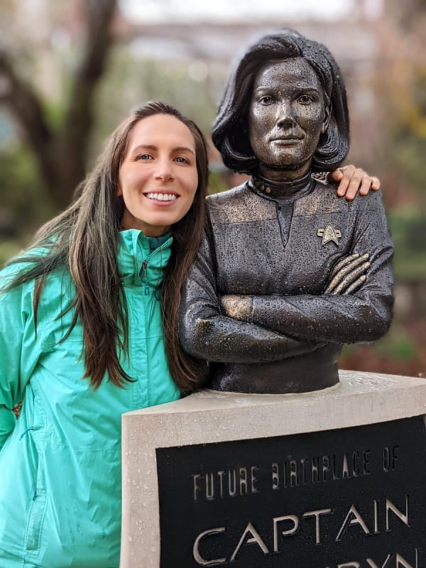 A woman stands with her arm around a statue of a Star Trek captain.