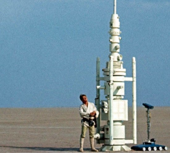A scene from Star Wars where a person stands in the desert next to a tall round device.