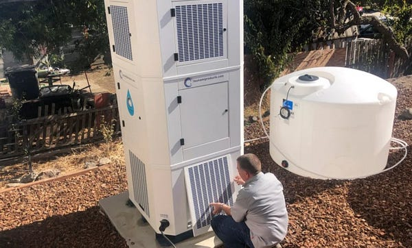 A person works on a large box that looks like a 10' tall air conditioner.  It's connected to a water tank.